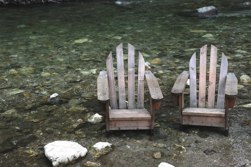 Old wooden adirondack chairs in a river bed, Big Sur, CA. stock images