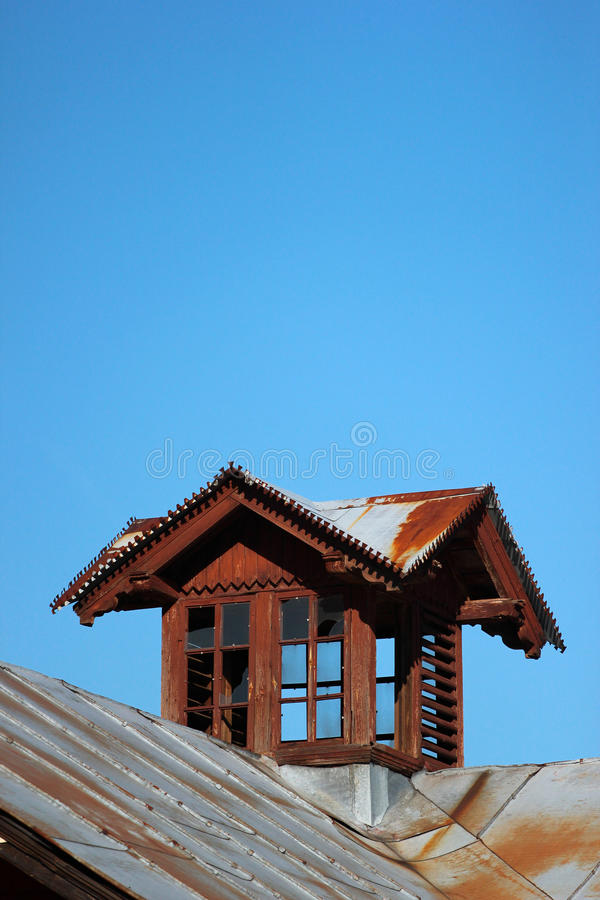 Old wooden attic window on metal roof royalty free stock photos