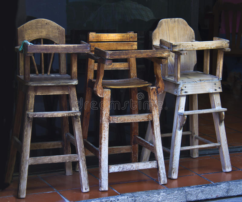 Old wooden baby highchairs in the restaurant royalty free stock photos