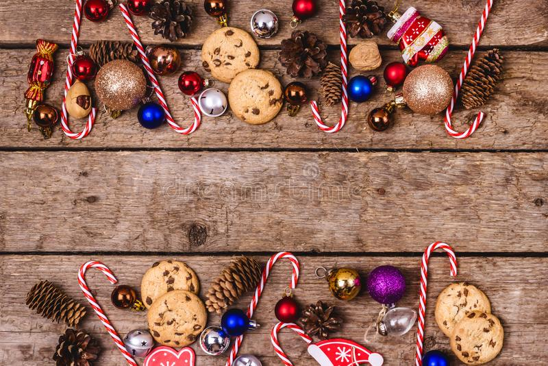 Old Wooden Background with Christmas Decorations Cookies with Chocolate Drops Red Brown and Lilac Small Christmas Balls Candy royalty free stock image
