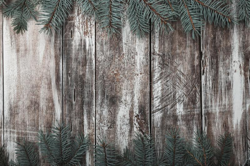 Old wooden background. Green fir branches at the top and bottom. Space for congratulation message of Xmas, Christmas and New Year. Rustic. Xmas and Happy New stock photo