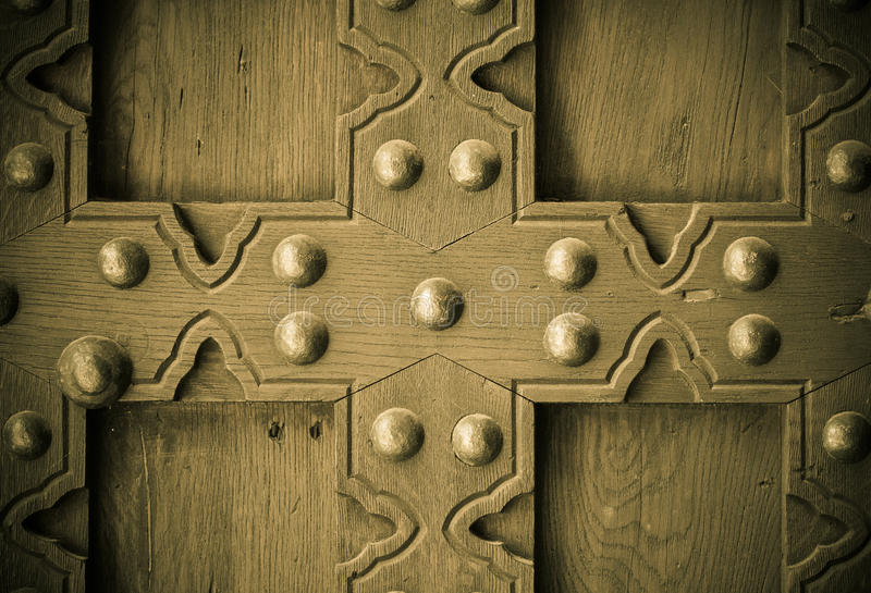 Old wooden background with metal rivets vintage door detail. Vintage grunge wooden background door gate of the old castle detail with metal rivets stock photos