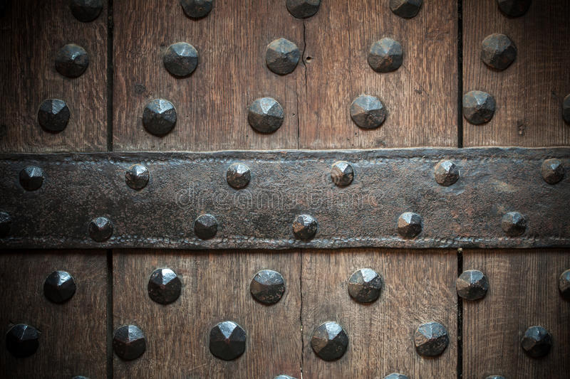 Old wooden background with metal rivets. Vintage grunge wooden background door gate of the old castle detail with metal rivets stock images