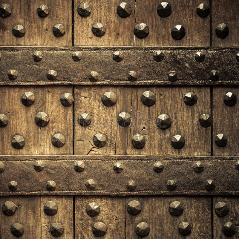Old wooden background with metal rivets. Vintage grunge wooden background door gate of the old castle detail with metal rivets. Square format stock photos