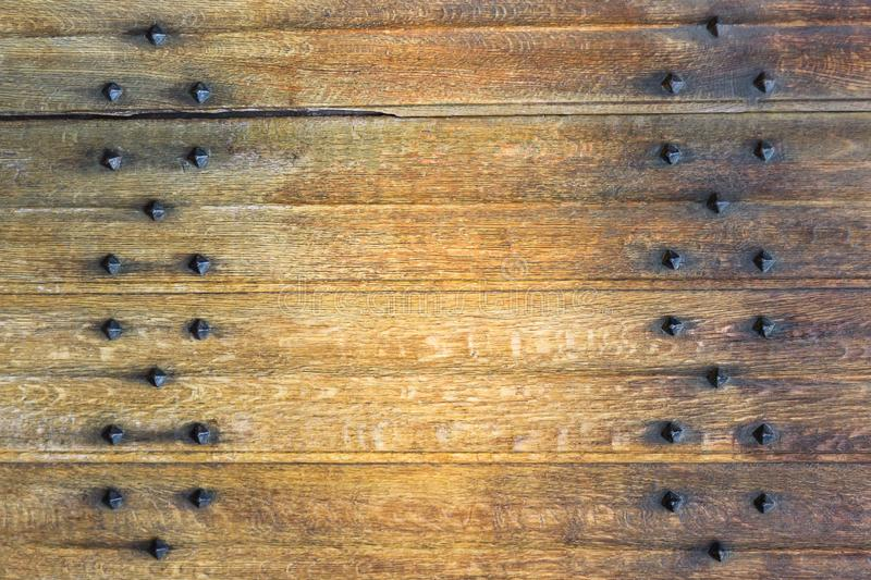 Old wooden background with metal rivets. Vintage wooden doors. Details stock photos