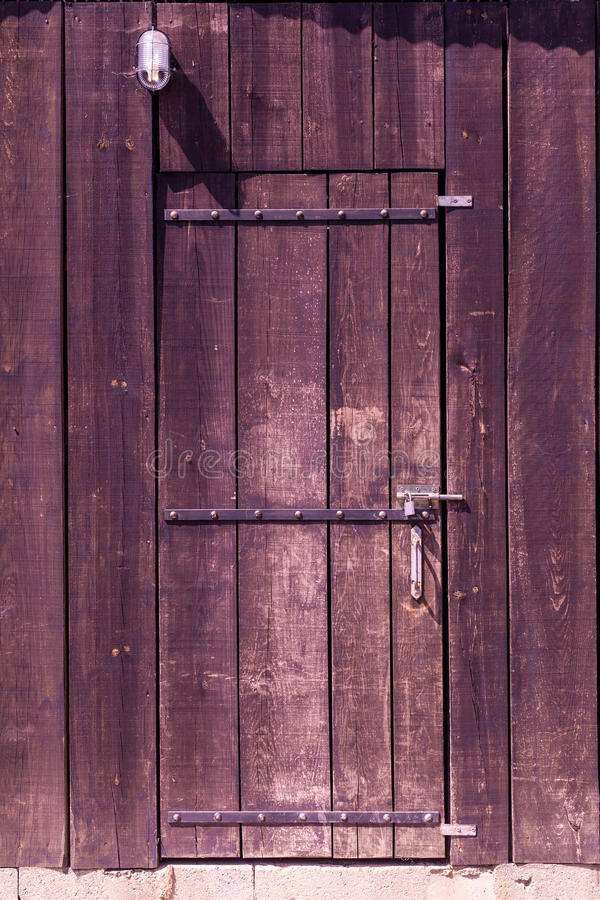 Old wooden barn door. Old wooden barn locked door with lamp royalty free stock images