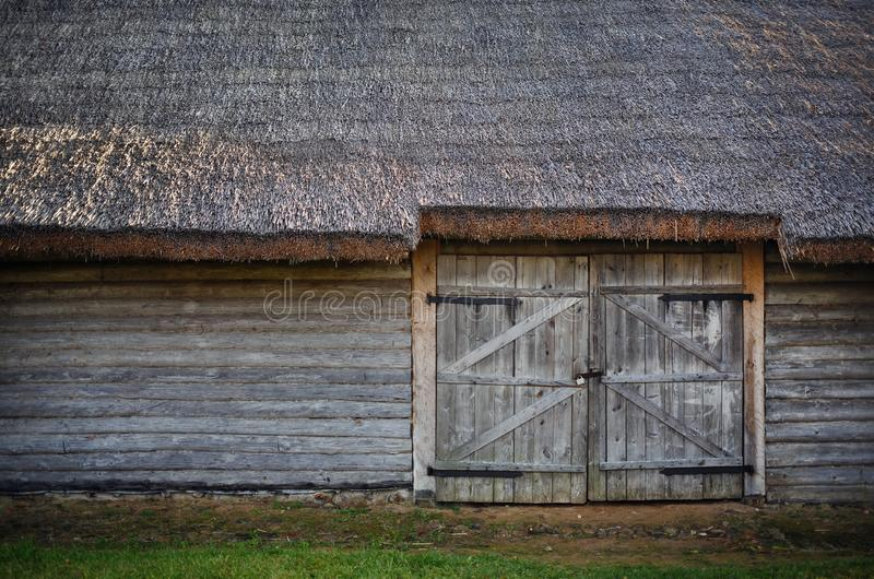 Old wooden barn. Log wall, gate and thatched roof royalty free stock photo