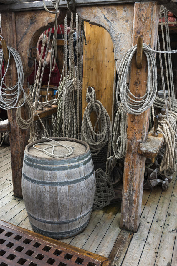Old wooden barrel on ships deck. Old wooden barrel and rigging ropes on the deck of a replica 18th century Tall Ship royalty free stock images