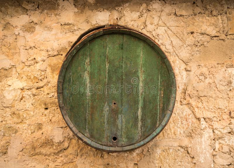 Wooden barrel hanging on old rustic stone wall of farmhouse. Old wooden barrel on stone farmhouse wall stock photos