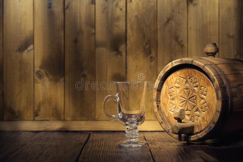 Old wooden barrel with a tap and an empty glass cup in the twilight on a wooden background royalty free stock image