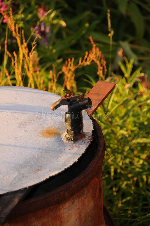 An old water barrel in a field on a beautiful summer evening in Norway royalty free stock photo