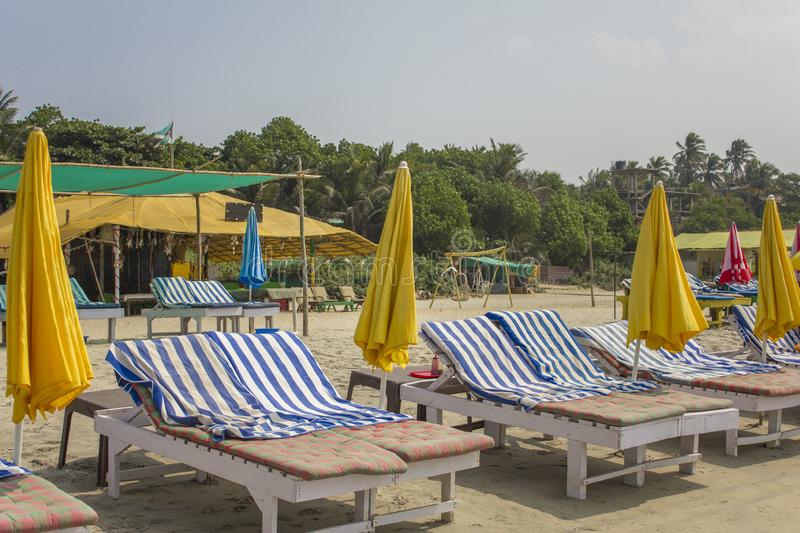 Old wooden beach beds with blue striped mattresses and yellow umbrellas on the sand against the background of green trees and huts stock photography
