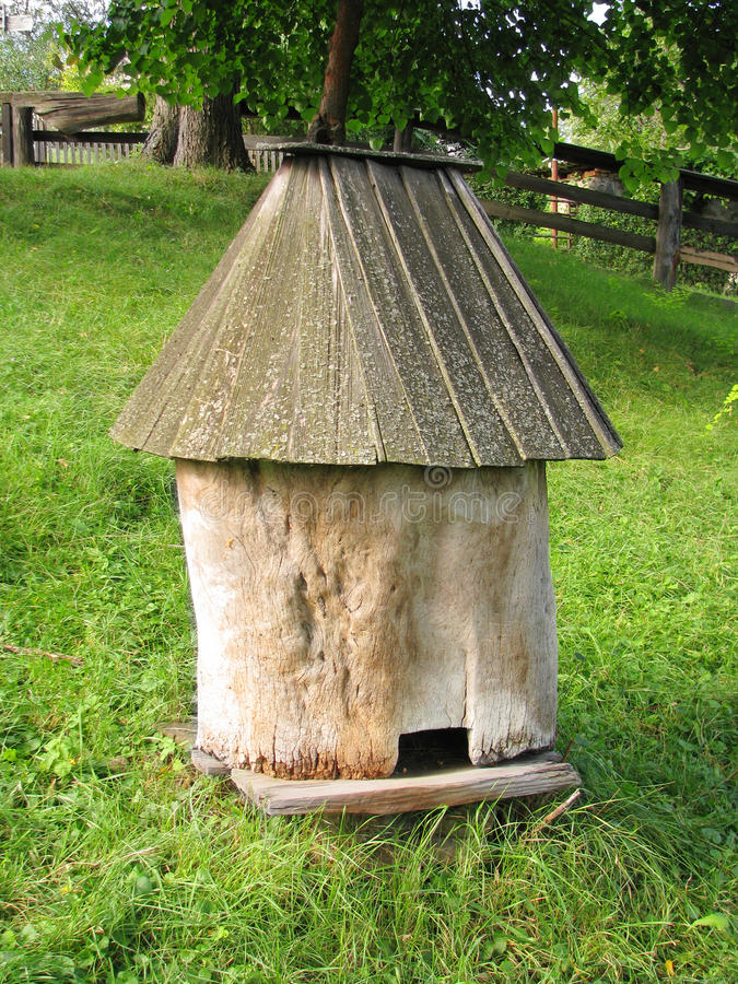 Old wooden bee hive. On a background of green grass royalty free stock image