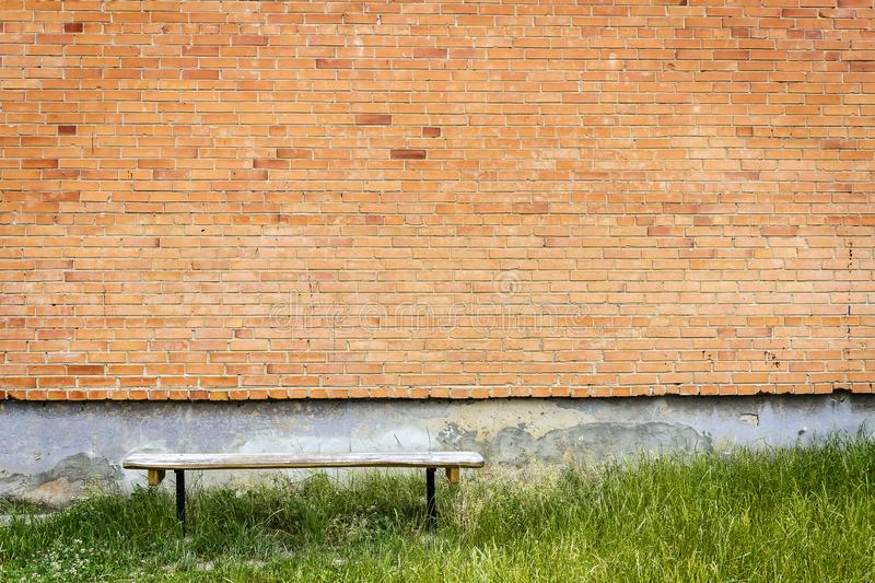 Old wooden bench by red brick wall stock image