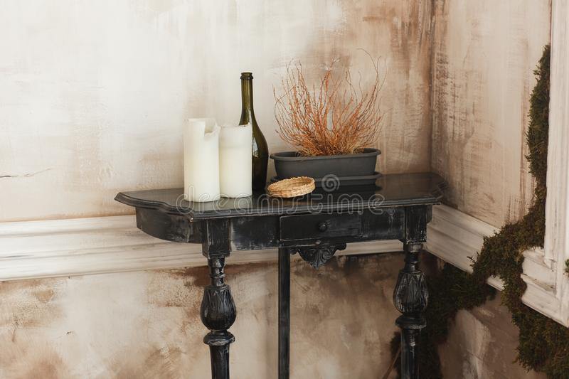 Old wooden black coffee table, candles, glass bottle flower pot in a corner of ancient room. Living interior and home royalty free stock photo