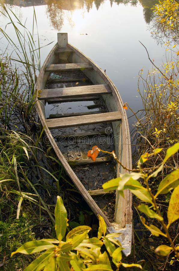Old wooden boat locked at lake. Morning scene. stock photo