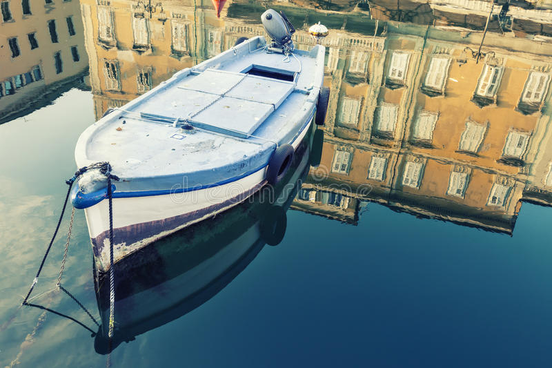 Old wooden boat, sky and ancient historical and building with reflection on blue water. Old wooden boat, sky and ancient historical building with reflection on royalty free stock image