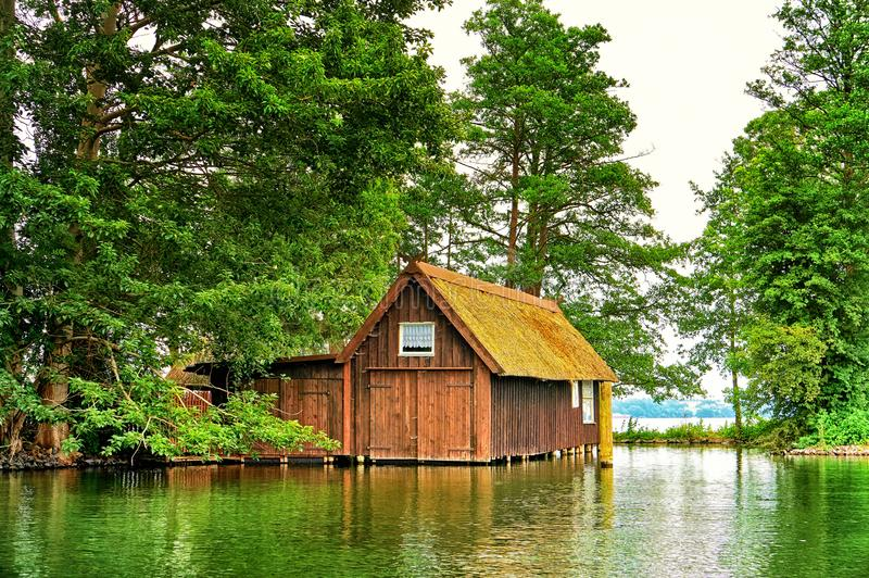 Old wooden boathouse with small window under trees at Schweriner See. Mecklenburg-Vorpommern Germany stock photos
