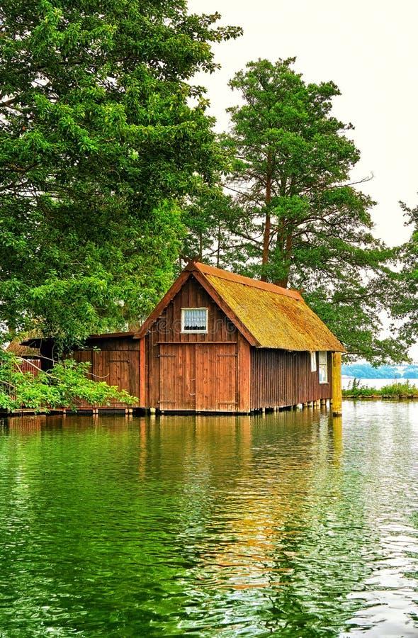 Old wooden boathouse under trees at Schwerin lake. Mecklenburg-Western Pomerania, Germany. Summer, sunset, landscape, travel, nature, sea, europe, destination stock images