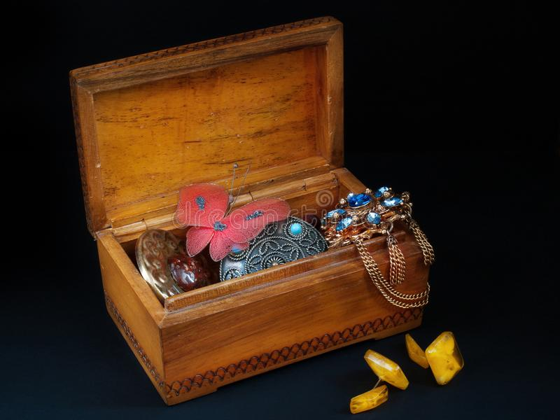 Old wooden box with broken ornaments on a black background royalty free stock images