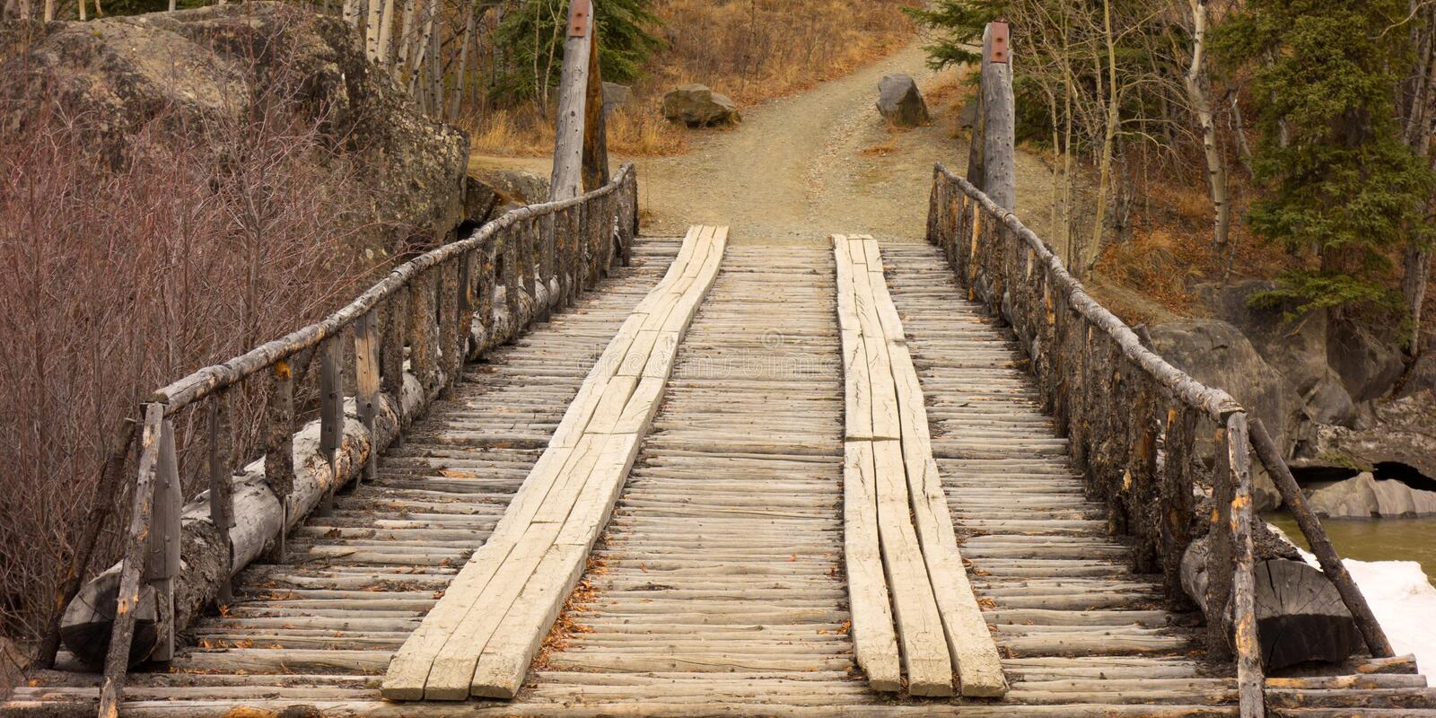 A rickety river crossing in northern canada. An old wooden bridge as seen in the yukon territories royalty free stock photography