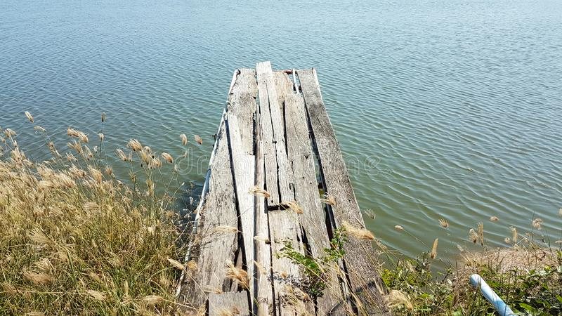 Old wooden bridge on the bank of the pond. Around with spread grasses royalty free stock photos