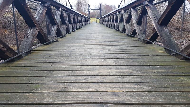 An old wooden bridge. Old wooden bridge autumn fall wet rainy gloomy moody dark background walking walkway river royalty free stock photos