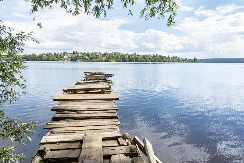 Old wooden bridge on the river bank. Rustic bridge of boards.  stock photo