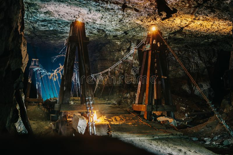 Old wooden bridge in scary abandoned underground limestone mine cave or tunnel or dark corridor with mysterious illumination stock images