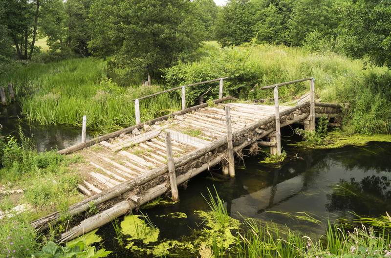 Old wooden bridge through stream stock images