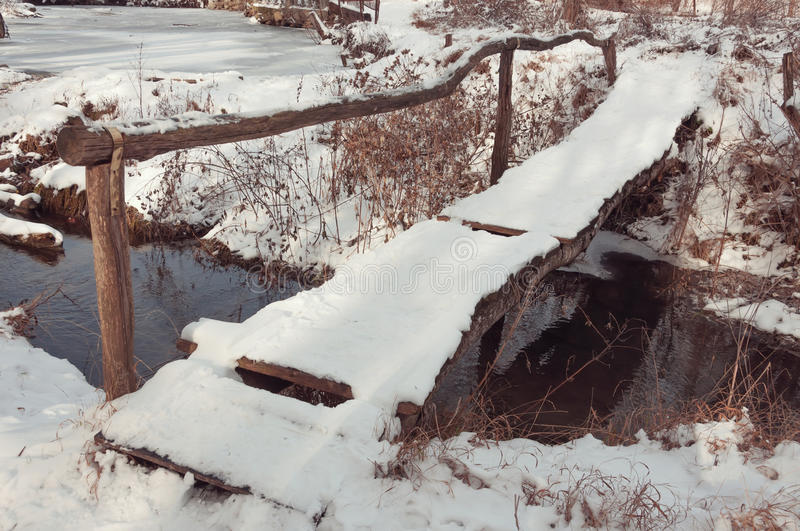 Old wooden bridge in winter. Old homemade wooden bridge across the river in winter village royalty free stock photos