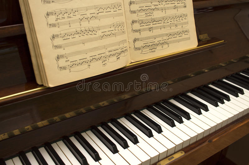 Old wooden brown classic piano with stave and music. Keyboard piano, side view of instrument stock photo