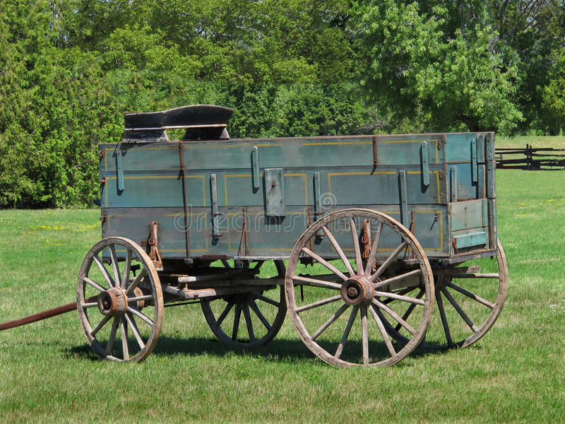 Old wooden buckboard farm wagon. Close-up of an old wooden buckboard horse drawn farm wagon, sitting in a pasture with trees in the background stock photography