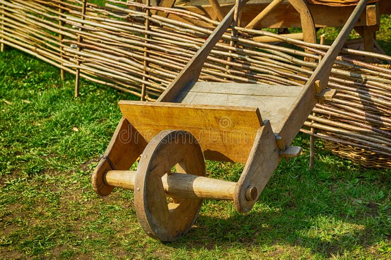 An old wooden car light brown with one wheel in the center stands on the lawn stock images