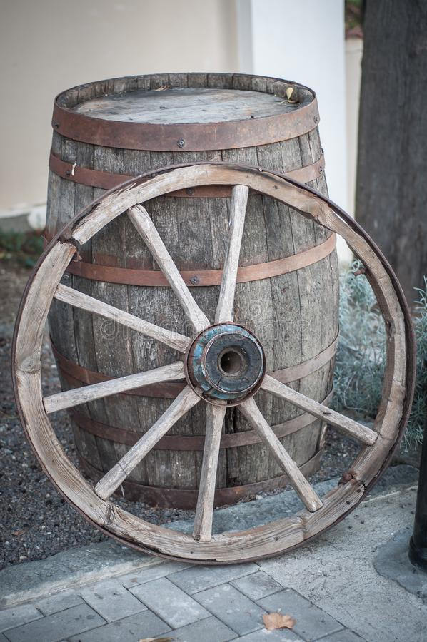 An old wooden cartwheel stands by a wooden barrel.  stock image