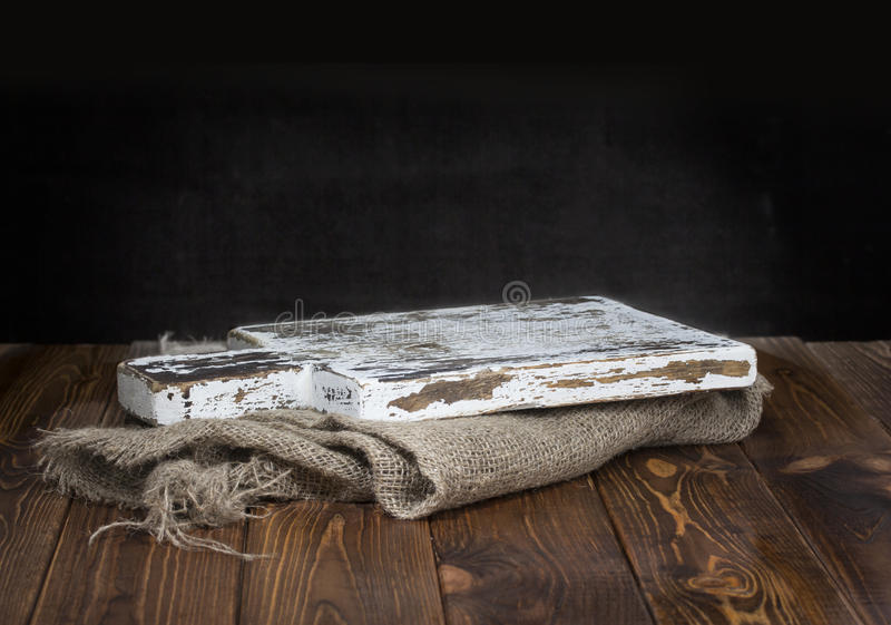 Old wooden chopping board with burlap tablecloth stock photos