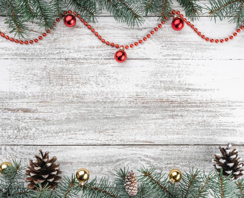 Old wooden Christmas background. Fir branches and cones. Gold and red baubles and garlands. Top view. Space for your text. Xmas. Card stock photography