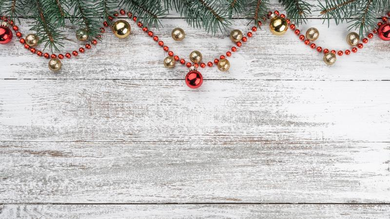 Old wooden Christmas background. Fir branches. Gold and red baubles. Red garlands. Top view. Space for your text. Xmas card. Horizontally card royalty free stock image