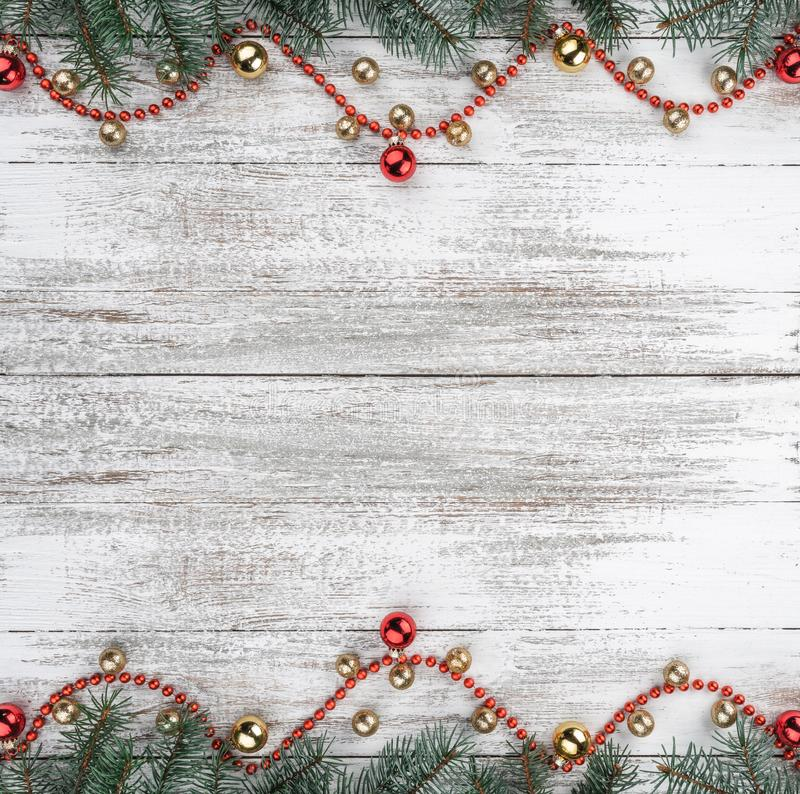 Old wooden Christmas background. Fir branches. Gold and red baubles. Red garlands. Top view. Space for your text. Xmas square card.  royalty free stock image