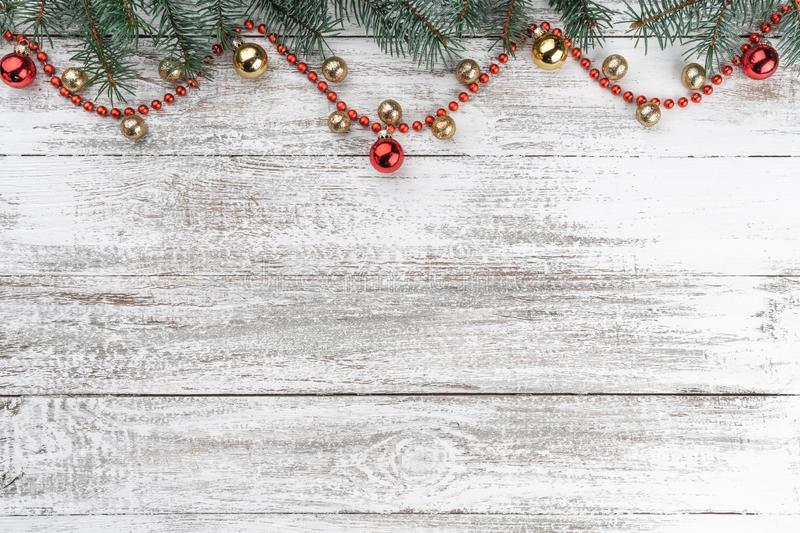 Old wooden Christmas background. Fir branches. Gold and red baubles. Red garlands. Xmas card. Top view. Space for your text.  stock photos