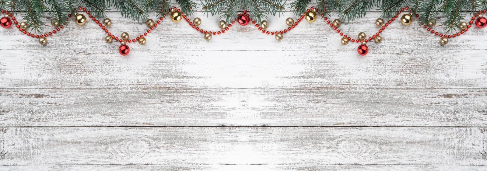 Old wooden Christmas background. Fir branches. Gold and red baubles. Red garlands. Xmas card. Top view. Space for your text. Horizontally card royalty free stock images