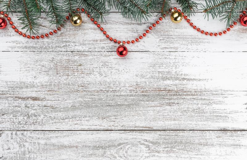 Old wooden Christmas background. Fir branches. Gold and red baubles. Red garlands. Xmas card. Top view. Space for your text. Horizontally card stock photo