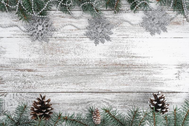Old wooden Christmas background. Garlands and snowflakes. Fir branches and cones. Xmas greeting card. Top view royalty free stock images