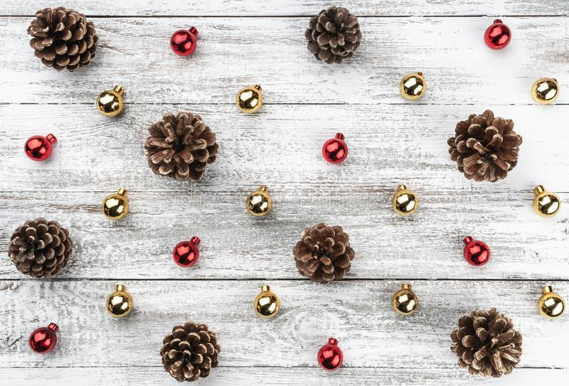 Old wooden Christmas background. Red and gold baubles and cones. Top view.  royalty free stock images