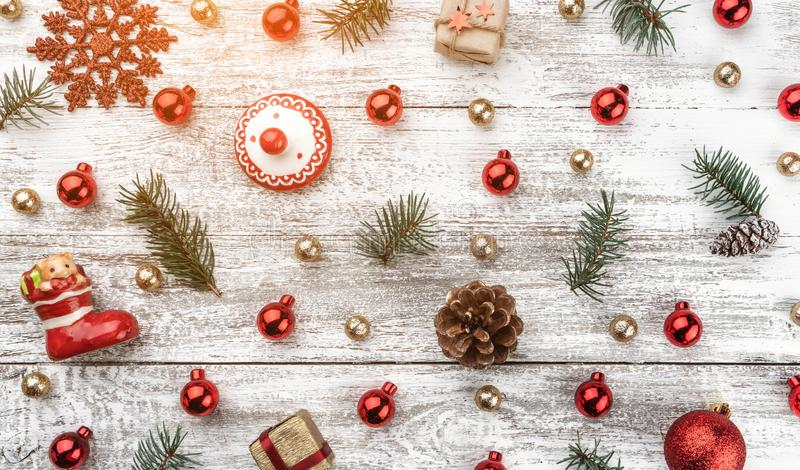 Old wooden Christmas background. Red and gold Baubles. Fir branches and cones. Xmas items. Top view. Light effect.  royalty free stock image