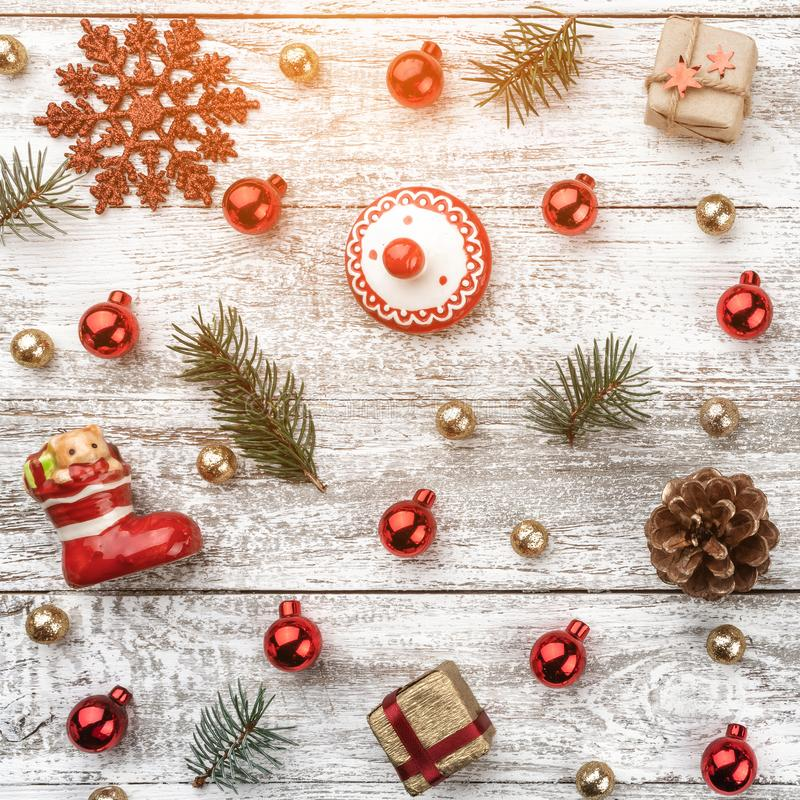 Old wooden Christmas background. Red and gold Baubles. Fir branches and cones. Xmas items. Top view. Light effect.  royalty free stock photos