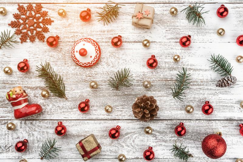 Old wooden Christmas background. Red and gold Baubles. Fir branches and cones. Xmas items. Top view. Light effect.  royalty free stock images