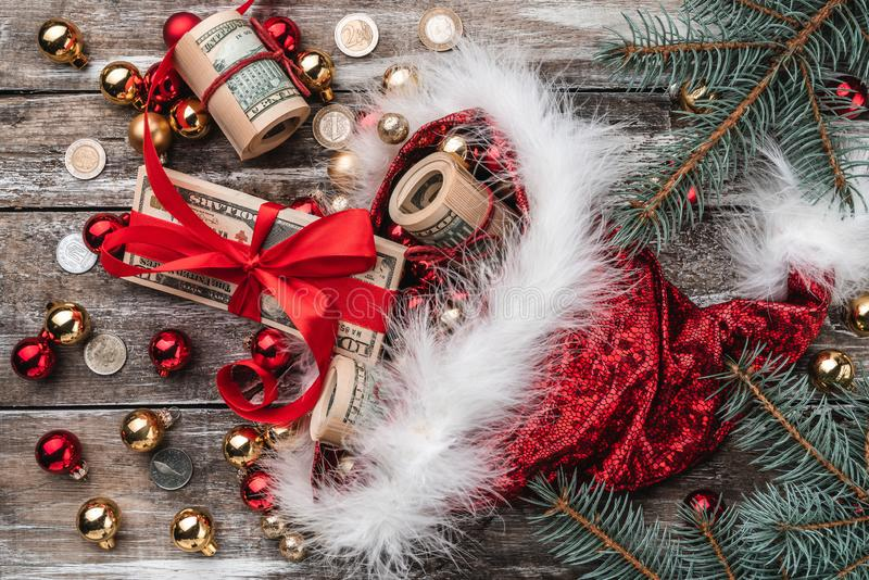 Old wooden Christmas background, Santa Claus, baubles and money coins and Xmas items. Top view.  royalty free stock image