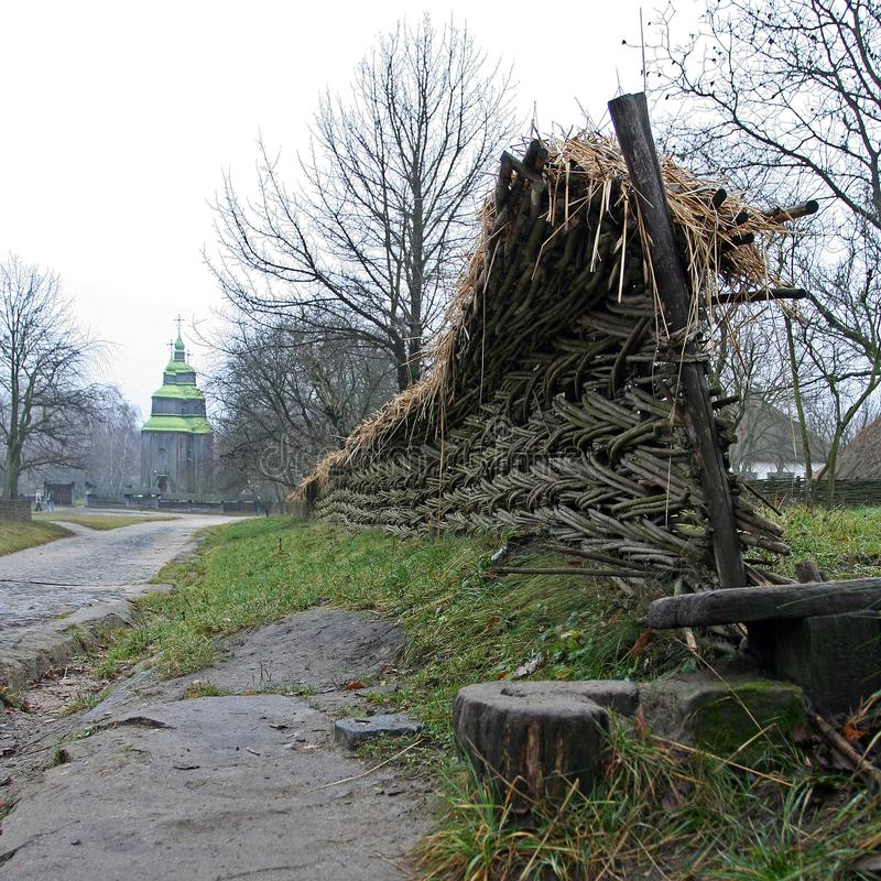 Old wooden church and wicker fence in the village stock photo