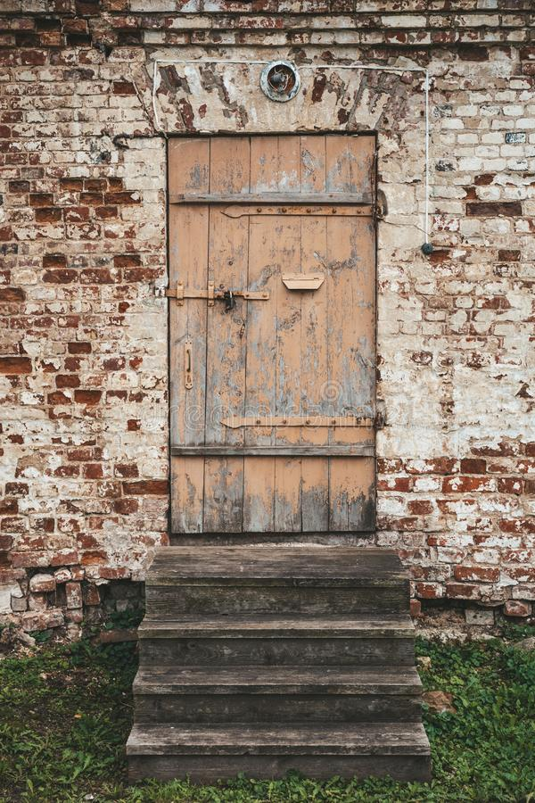 Old wooden closed door and steps in ancient brick building wall royalty free stock photo